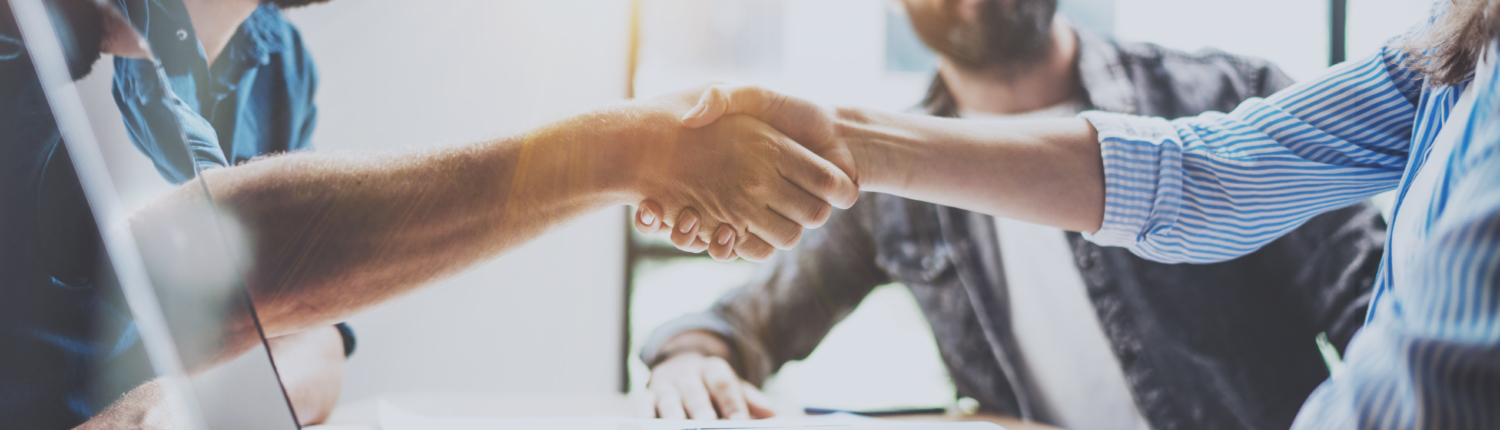 Business partnership handshake concept.Photo two coworkers handshaking process.Successful deal after great meeting.Horizontal, blurred background.Wide.